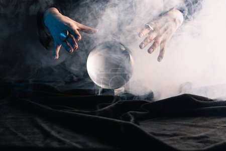 Photo for Cropped view of witch performing ritual with crystal ball on dark background - Royalty Free Image