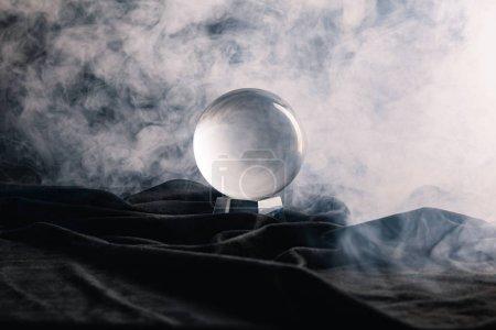 Photo pour Boule de cristal sur textile avec fumée sur fond sombre - image libre de droit