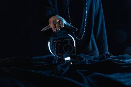 Photo pour Vue recadrée de la main féminine touchant boule de cristal sur fond noir - image libre de droit