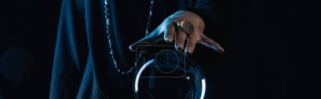 Photo for Cropped view of female hand touching crystal ball on black background, panoramic shot - Royalty Free Image