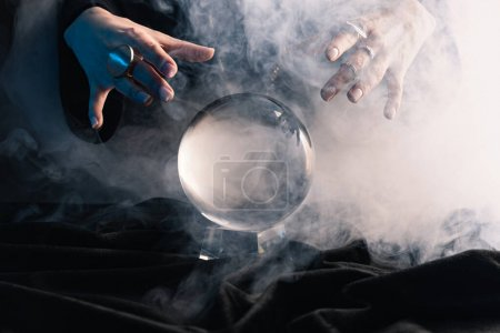 Photo for Cropped view of female hands above crystal ball with smoke on dark - Royalty Free Image