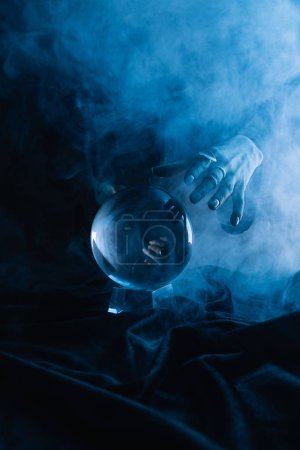 Photo for Cropped view of female hand above crystal ball with smoke on dark blue - Royalty Free Image