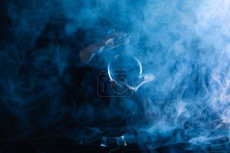 Photo pour Vue recadrée de la sorcière tenant une boule de cristal avec de la fumée autour sur bleu foncé - image libre de droit