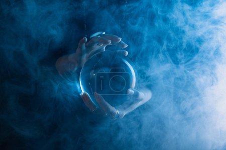 Photo pour Vue partielle de la sorcière tenant une boule de cristal avec de la fumée autour sur bleu foncé - image libre de droit