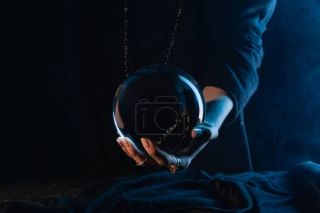 Photo for Partial view of crystal ball in female hand on dark blue - Royalty Free Image