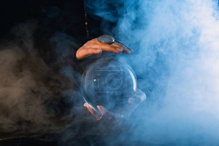 Photo for Partial view of female hands with crystal ball and smoke around on dark blue - Royalty Free Image