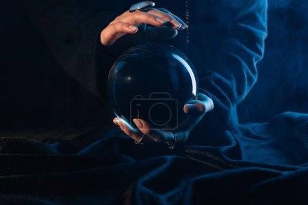 Photo pour Vue partielle de la sorcière avec boule de cristal sur bleu foncé - image libre de droit