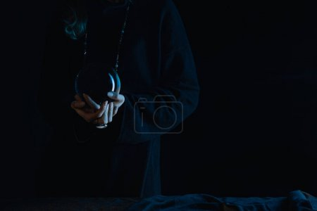 Photo for Cropped view of witch with clenched hands holding crystal ball on black background - Royalty Free Image