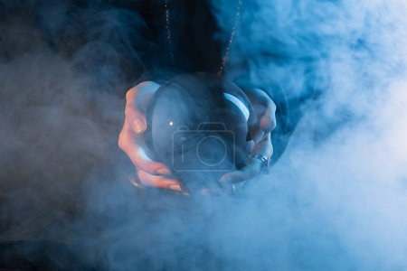 Photo for Partial view of female hands with crystal ball and smoke around on dark blue background - Royalty Free Image