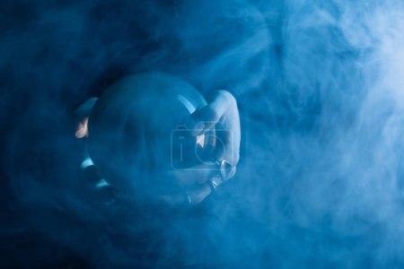 Photo for Cropped view of female hands with crystal ball and smoke around on dark blue background - Royalty Free Image