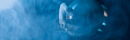 Photo for Cropped view of female hands with crystal ball and smoke around on dark blue background, panoramic shot - Royalty Free Image