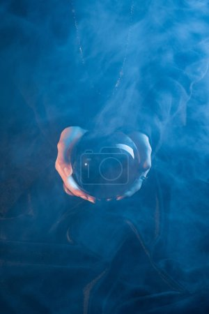 Photo pour Vue recadrée de sorcière tenant une boule de cristal au-dessus de la table sur fond bleu foncé - image libre de droit