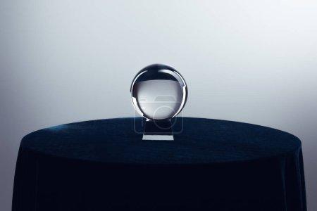 Photo pour Boule de cristal sur table ronde sur fond gris - image libre de droit