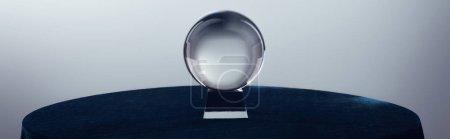 Foto de Bola de cristal sobre mesa redonda sobre fondo gris, plano panorámico - Imagen libre de derechos