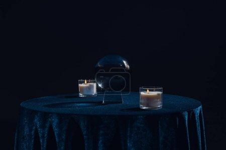 Photo pour Boule de cristal avec bougies sur table isolée sur noir - image libre de droit