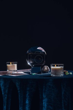 Photo for KYIV, UKRAINE - JANUARY 9, 2020: crystal ball with occult objects on round table isolated on black - Royalty Free Image