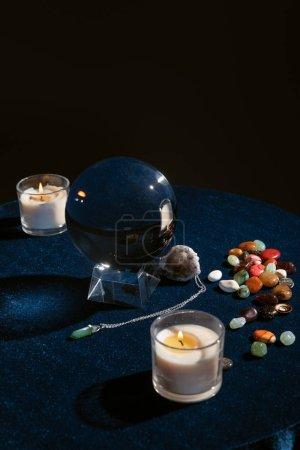 Foto de Bola de cristal con velas y objetos ocultos en mesa redonda aislada en negro - Imagen libre de derechos
