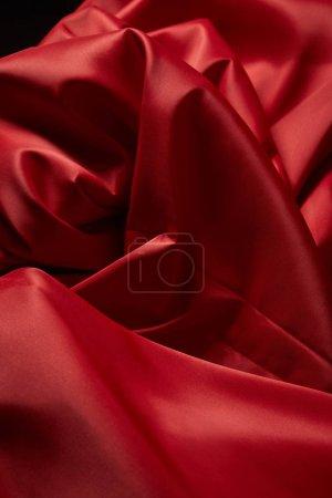 Photo pour Vue de près d'un tissu de soie rouge mou et émietté isolé sur noir - image libre de droit