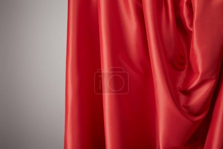 Photo for Close up view of red soft and wavy silk textured cloth on grey background - Royalty Free Image