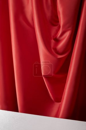 Photo for Close up view of red soft and wavy silk textured cloth and white surface - Royalty Free Image