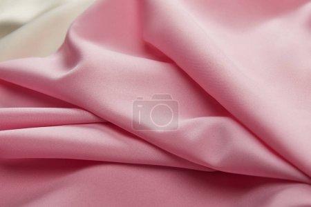 Photo pour Vue de près des tissus mous et ondulés roses et blancs satinés - image libre de droit