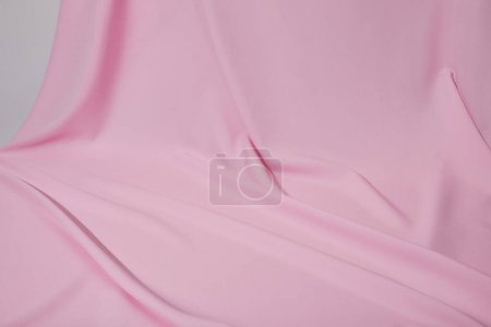 close up view of pink soft wavy fabric isolated on grey