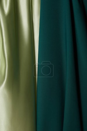 close up view of emerald, light green soft and wavy silk fabric
