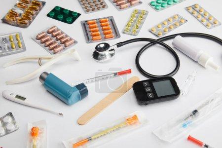 Photo pour Vue grand angle des médicaments colorés, stéthoscope, thermomètre et objets médicaux sur blanc - image libre de droit