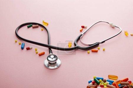 Photo pour Vue grand angle du stéthoscope et des médicaments colorés brillants sur rose - image libre de droit