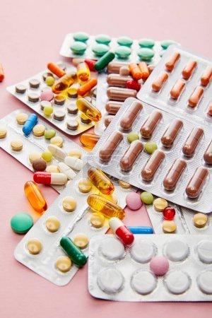 Selektive Fokussierung bunter Arzneimittel auf rosa Hintergrund