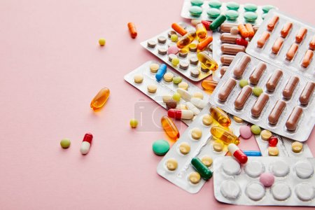 Photo pour Vue grand angle des médicaments colorés sur rose - image libre de droit