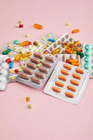 Photo pour Vue grand angle des capsules et pilules colorées sur rose - image libre de droit