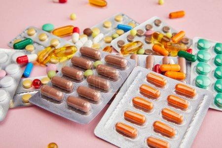 Photo pour Concentration sélective de capsules et pilules colorées sur le rose - image libre de droit