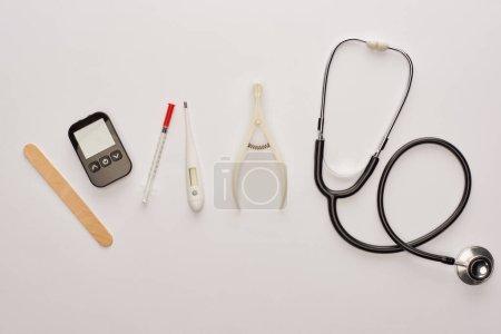 Photo pour Vue de dessus du stéthoscope et des objets médicaux sur fond blanc - image libre de droit