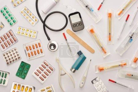 Photo pour Vue du dessus des pilules, seringues et objets médicaux sur fond blanc - image libre de droit