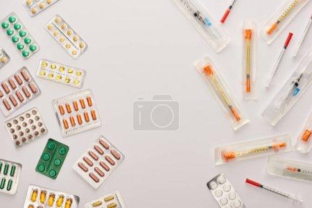 Photo pour Vue du dessus des pilules et seringues sur fond blanc - image libre de droit