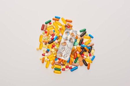 Photo pour Vue du dessus de la plaquette thermoformée vide sur le cœur à partir de pilules colorées isolées sur blanc - image libre de droit