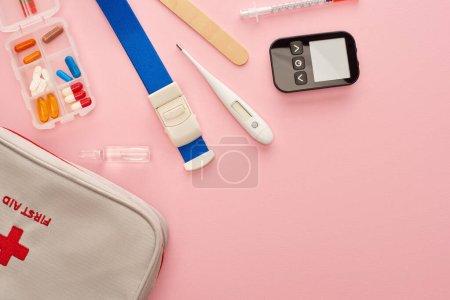 Photo pour Vue du dessus de la trousse de premiers soins, des pilules et des objets médicaux sur rose - image libre de droit
