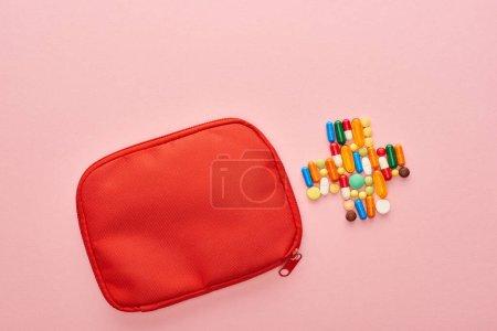 Photo pour Vue du dessus de la trousse de premiers soins rouge et croix de pilules sur fond rose - image libre de droit
