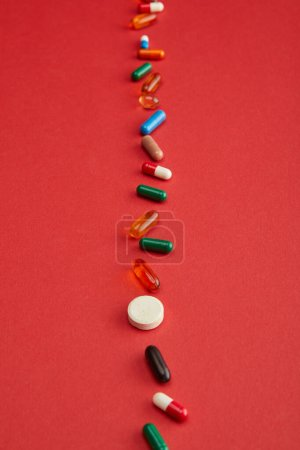 Photo for High angle view of bright pills on red background - Royalty Free Image