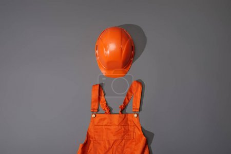 Photo for Top view of orange helmet and overalls on grey background - Royalty Free Image