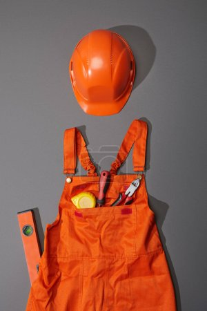 Photo for Top view of orange helmet and overalls with measuring tape, screwdriver and pliers near spirit level on grey background - Royalty Free Image