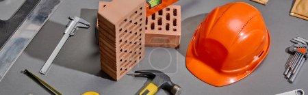 Photo pour Plan panoramique de briques, marteau, clés d'angle, casque orange, étriers et couteau à mastic sur fond gris - image libre de droit
