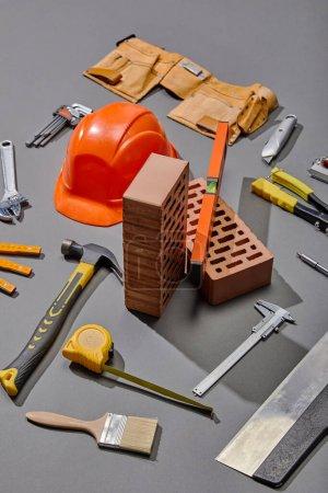 Photo pour Vue grand angle des briques, des outils industriels et du casque sur fond gris - image libre de droit