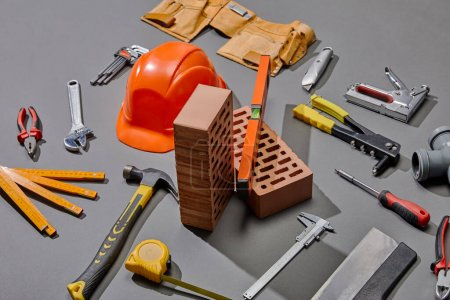 high angle view of helmet, bricks and industrial tools on grey background