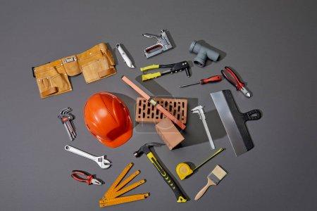widok z góry cegieł, paska narzędziowego, kasku i narzędzi przemysłowych na szarym tle