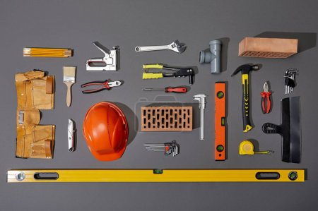 Photo for Flat lay with bricks, orange helmet, tool belt and industrial tools on grey background - Royalty Free Image