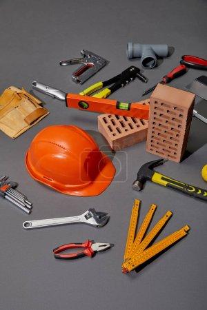 Blick auf Werkzeuggürtel, Ziegel, Industriewerkzeuge und orangefarbenen Helm auf grauem Hintergrund