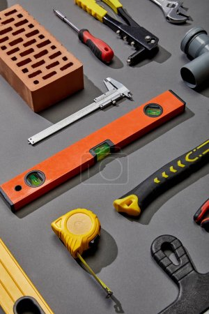 Photo for Flat lay with brick, measuring tape, spirit level, brick and industrial tools on grey background - Royalty Free Image