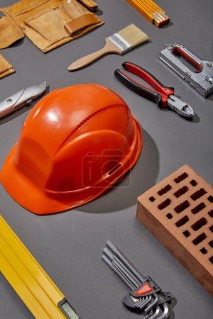 Photo pour Pose plate avec casque orange, brique, brosse, brique, ceinture à outils et outils industriels sur fond gris - image libre de droit